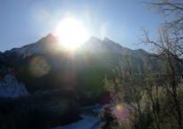 photo of sun rising behind mountain peaks