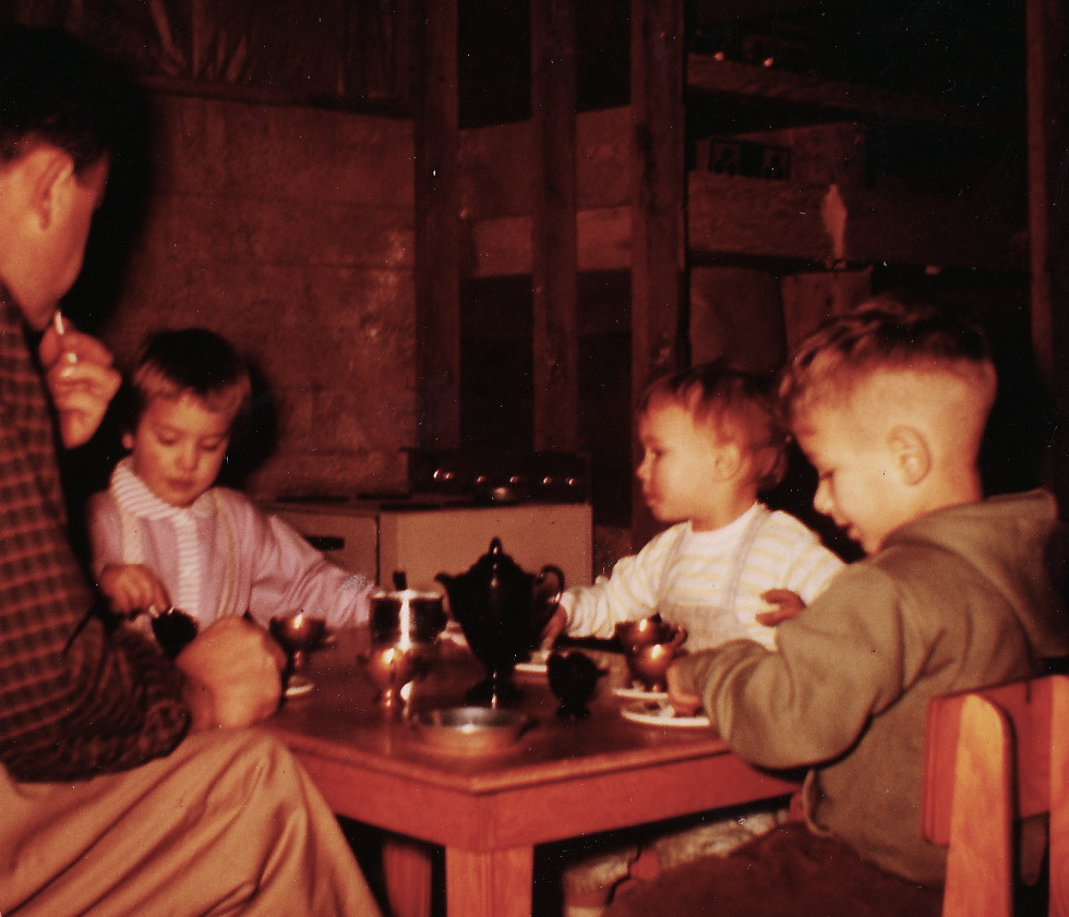 Dad having tea with us kids in the kitchen he built us circa 1964: table and chairs, cupboards, fridge, and a stove with real knobs. FisherPrice had nothing on Dad.