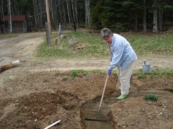 photo of gardener raking path